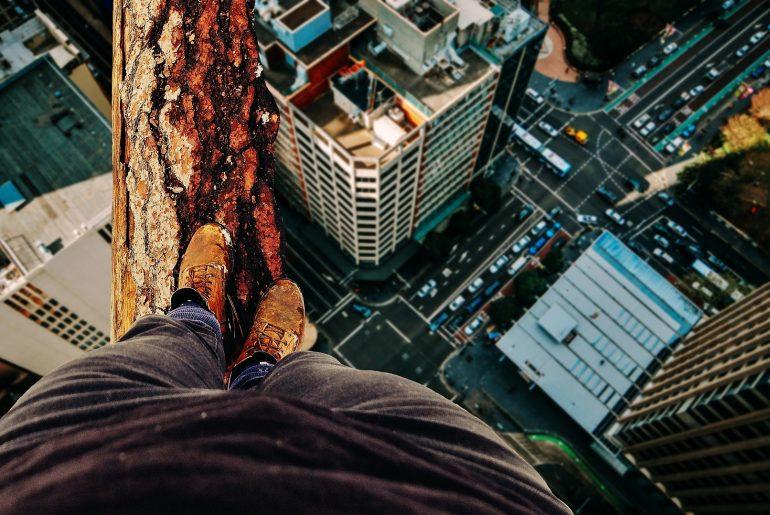 Mann balanciert auf Baumstamm.