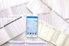 Verschiedene handschriftliche Fahrtenbücher und Smartphone mit Fahrtenbuch App von Vimcar.