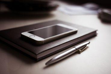 Notzizbuch und Smartphone auf einem Bürotisch.