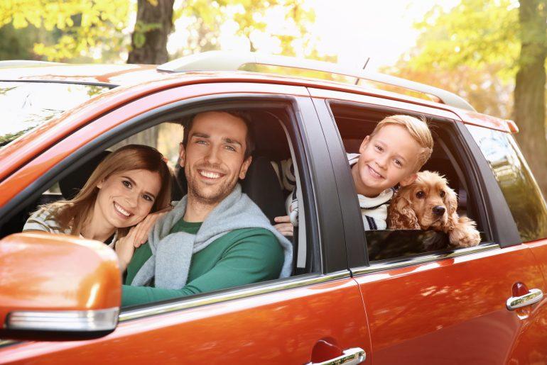 Familie sitzt in einem Auto und macht einen Ausflug.
