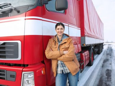 woman standing in front of red long haul truck with big fleet tracking