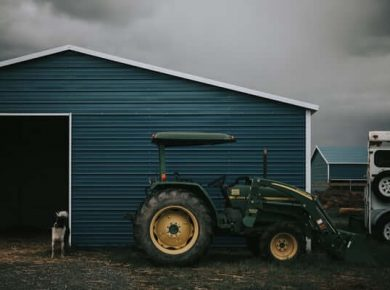 tractor tracker farm equipment in front of barn