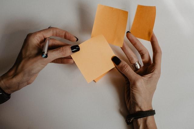 busy Transport Manager holding many orange sticky notes