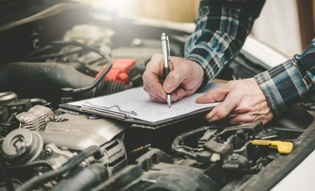 clipboard on car engine held by transport manager completing vehicle maintenance tasks