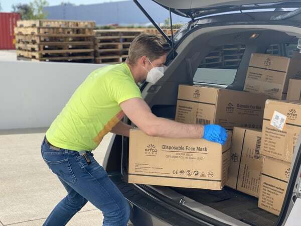 person wearing mask unloading delivery van