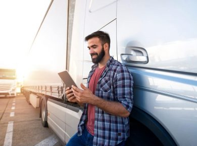 fleet manager standing by fleet truck using car tracking app on tablet