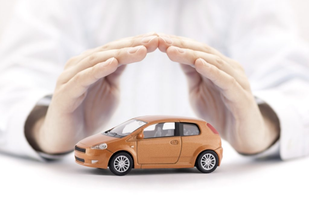 A hand covering a car representing pool car insurance