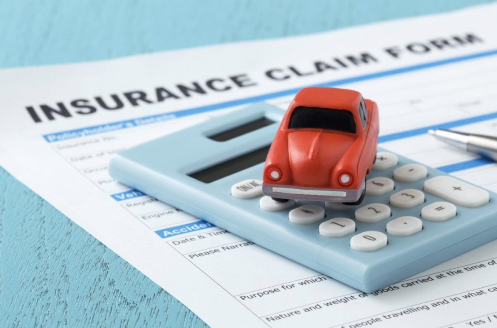 Car on a calculator and pool car insurance form