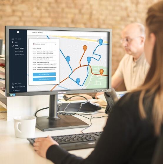 An employee using a GPS Fleet Tracker on a desktop computer