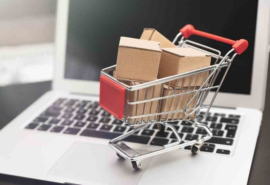 shoppping basket of packages on top of a laptop