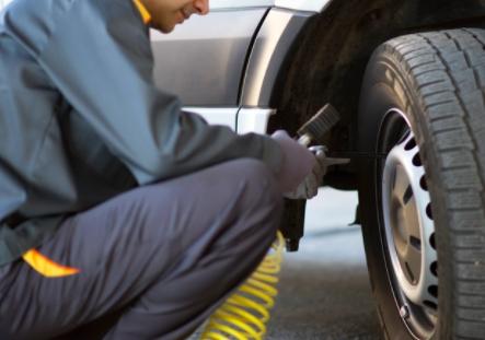 A van driver checking his van's tyres with a van check sheet