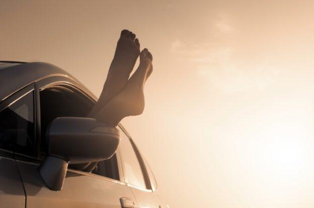Nackte Füße werden aus dem Autofenster gehängt.